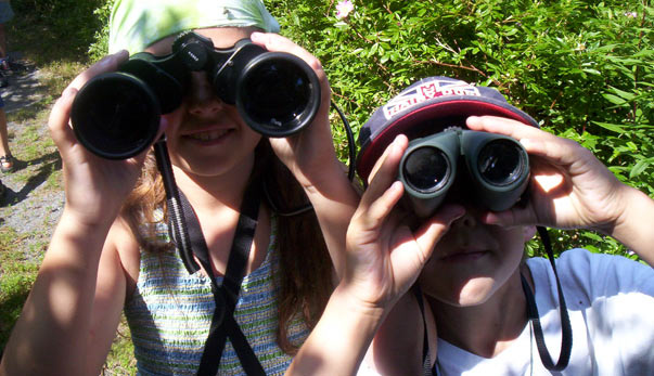 Two children looking through binoculars