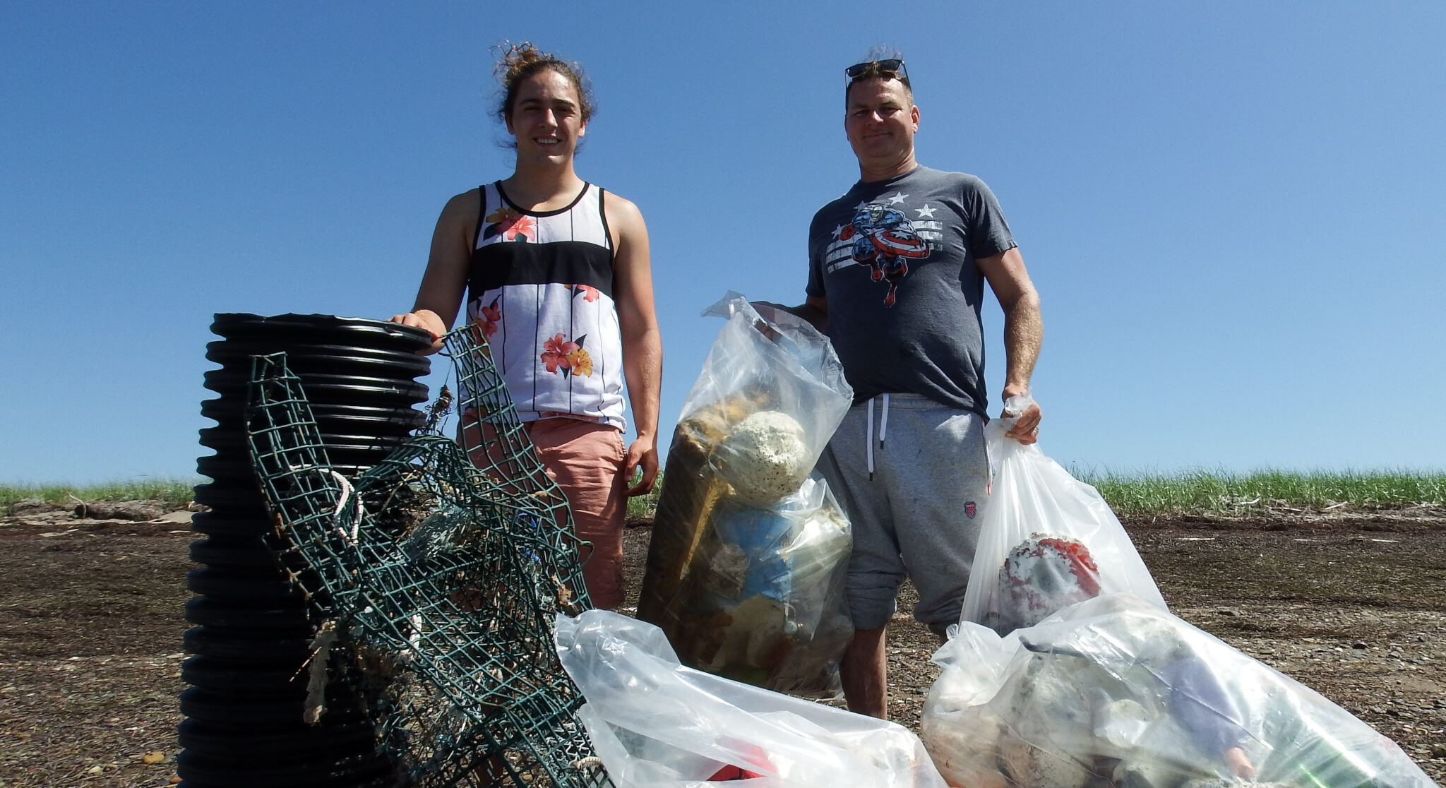Summer student and Lewnnany collect trash on the beach